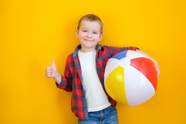 Summer vacation concept, portrait of happy cute little child, boy smiling and holding beach ball, child having fun with inflatable ball and showing like, studio shot isolated on yellow background