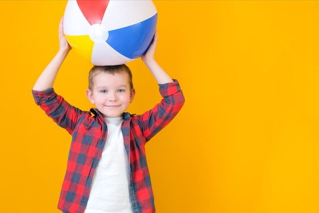 Summer vacation concept, portrait of happy cute little child, boy smiling and holding beach ball, child having fun with inflatable ball, studio shot isolated on yellow background