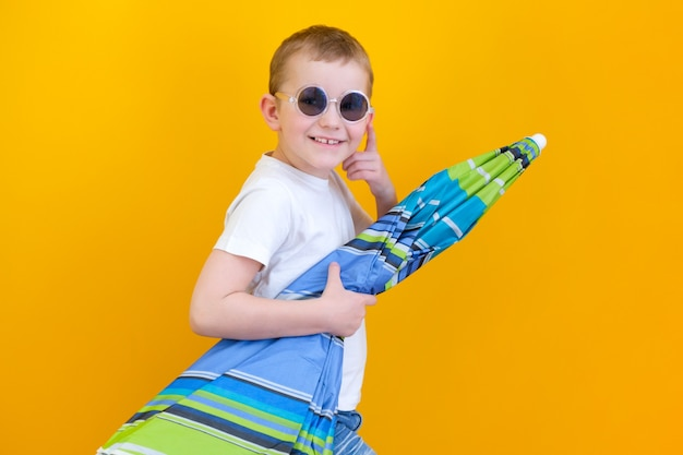 Summer vacation concept, portrait of happy cute little child, boy with glasses smiling and holding a beach umbrella, studio shot isolated on yellow background