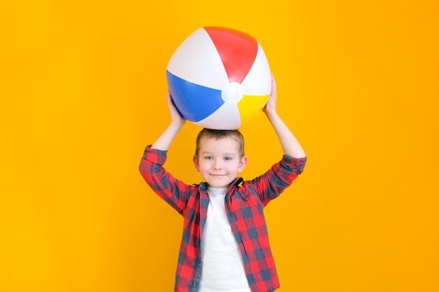 여름 휴가 개념, 행복한 귀여운 어린 아이의 초상화, 웃고 비치 볼을 들고 있는 소년, 풍선 공을 가지고 즐거운 시간을 보내는 아이, 노란색 배경에 격리된 스튜디오 촬영