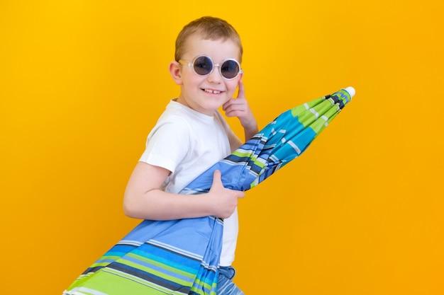 여름 휴가 개념, 행복한 귀여운 어린 아이의 초상화, 안경을 쓴 소년이 웃고 비치 파라솔을 들고 노란색 배경에 격리된 스튜디오 촬영