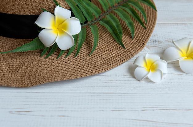 여름 휴가 개념입니다. 흰색 나무 바탕에 프랜지파니 꽃이 있는 밀짚 모자와 해변 액세서리