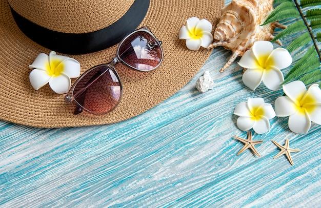 여름 휴가 개념입니다. 푸른 나무 배경에 조개와 불가사리가 있는 밀짚 모자와 해변 액세서리