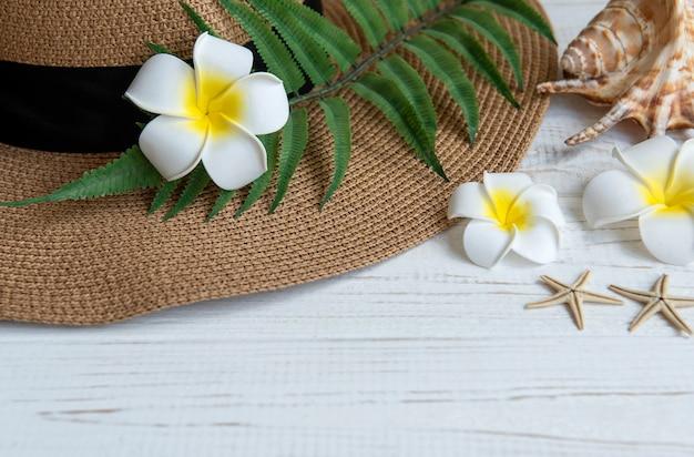 여름 휴가 개념입니다. 흰색 나무 배경에 조개와 불가사리가 있는 밀짚 모자와 해변 액세서리