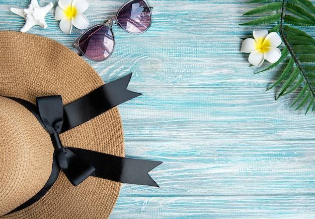 Summer vacation concept. straw hat and frangipani flowers on blue wooden background