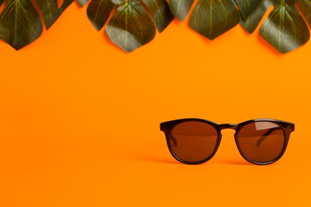 Summer and vacation concept. sunglasses and tropical leaves on a orange colored background