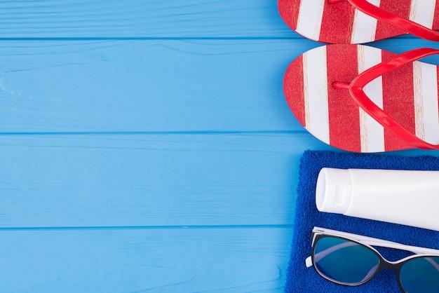 夏休みのコンセプト。上の俯瞰図のクローズアップ写真タオルサングラス日焼け止めとコピースペースと青い木製の背景で隔離のフリップフロップ