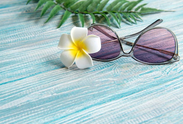 Summer vacation concept.  white frangipani flower, sunglasses on a blue wooden background