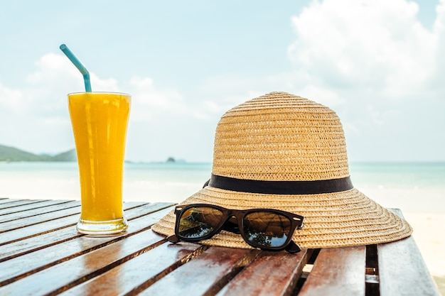 Summer vacation concept with glass of orange juice, hat and sunglasses over sea beach background