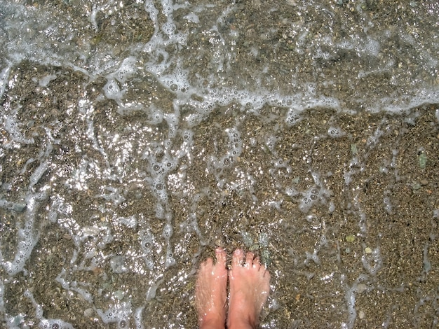 Summer vacation concept, woman feet toes in warm sea water and foam, pebbles beach, barefoot, top view