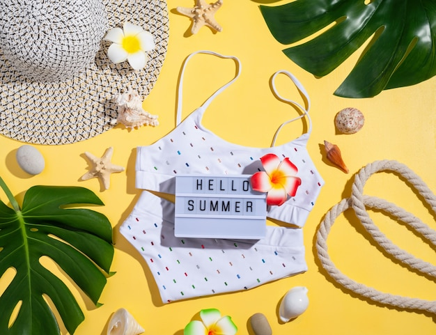 Summer and vacation concept. words hello summer on the lightbox with swimming suit, tropical leaves and seashells flat lay on orange background