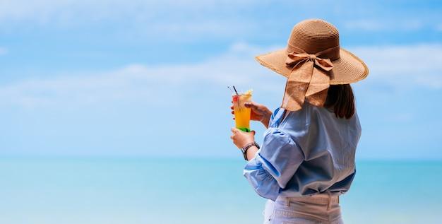 夏の休暇の概念スタイリッシュな青いドレスとビーチで青い空と麦わら帽子を着てカクテルを保持している若い女性。