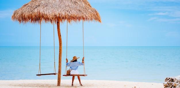 Концепция летних каникул молодая женщина в стильном синем платье и соломенной шляпе с голубым небом на пляже.