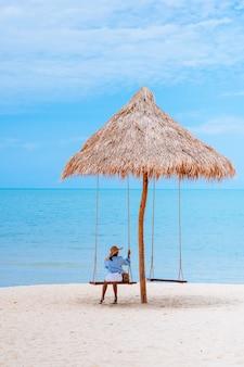 夏の休暇の概念スタイリッシュな青いドレスとビーチで青い空と麦わら帽子を身に着けている若い女性。