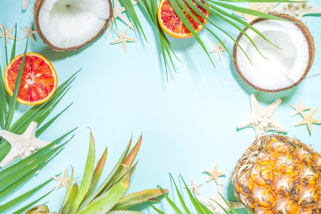 Summer vacation flat lay with with pineapple coconut orange fruit, palm leaves and sea shell