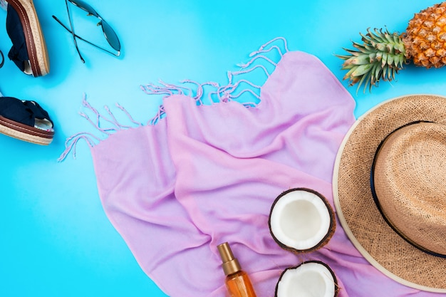Summer vacation flatlay with straw hat, pink scarf, pineapple, coconut, body oil, sandals and sunglasses on blue