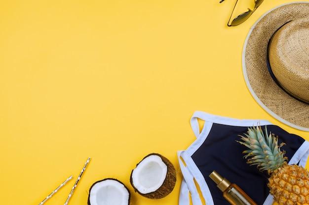 Летние каникулы с соломенной шляпой, купальником, половинками кокоса, маслом для тела и очками на желтом с copyspace