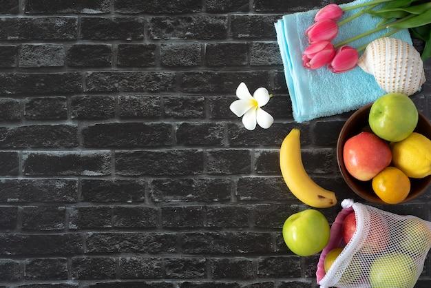 Летние каникулы фруктовый тюльпан и шляпа от солнца на фоне кирпичной стены, плоский вид сверху с копией пространства