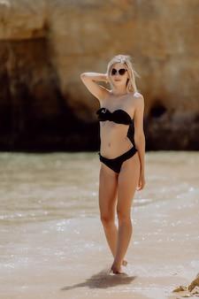 Donna allegra spensierata di felicità di vacanze estive che sta sulla sabbia bianca
