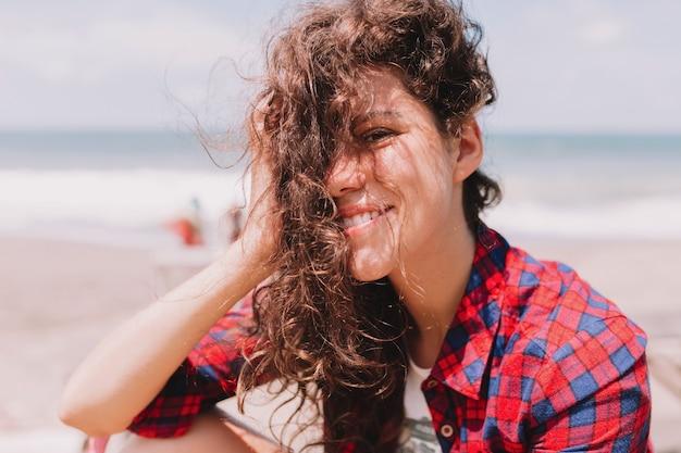 夏休み。海の岸に座ってウェーブのかかった髪を飛んで幸せな楽しい女性