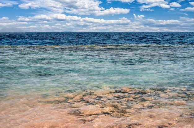 여름 휴가, 열대 해변과 푸른 바다와 태양 플레어가 있는 흰 구름의 휴가 배경