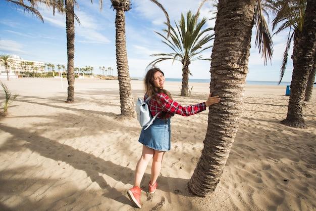 夏休み、休日、旅行のコンセプト-海沿いのヤシの木の枝の下で美しい若い女性。