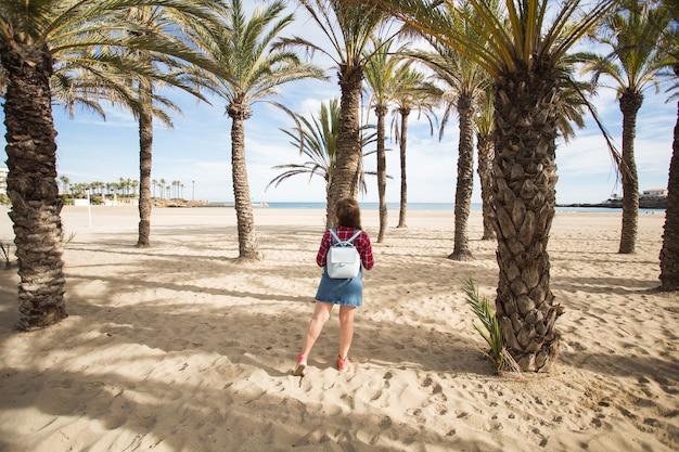 Летние каникулы, каникулы и концепция путешествий - красивая молодая женщина под ветвями пальмы