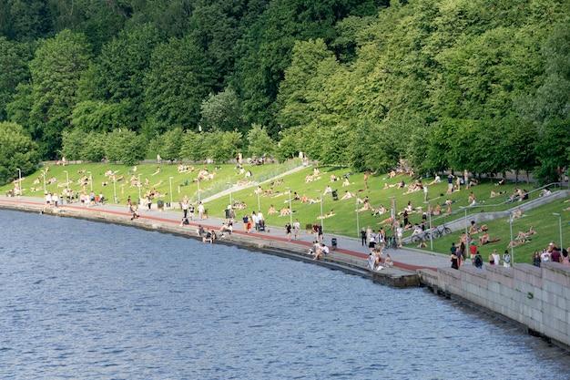 Летний отдых в москве. люди загорают на набережной москвы-реки летом в жаркий солнечный день.