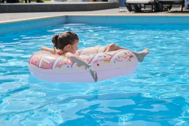 여름 휴가, 야외 수영장에서 수영 반지에 쉬고 어린 여자 아이, 스파 리조트 호텔