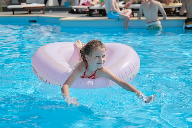 Summer vacation, little girl child resting on swimming ring in outdoor pool, spa resort hotel