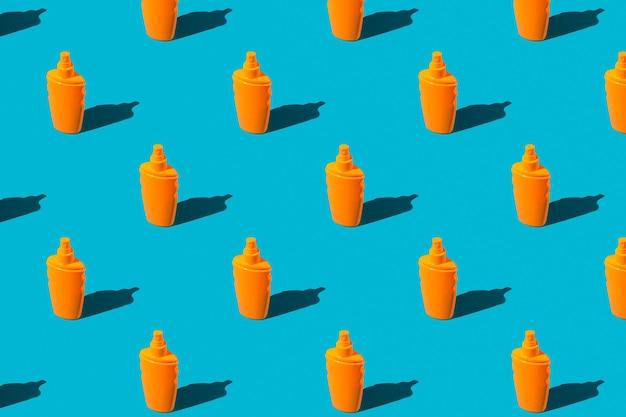 夏休みの最小限のコンセプト。青の背景にオレンジ色の日焼け止めローションボトルのパターン。