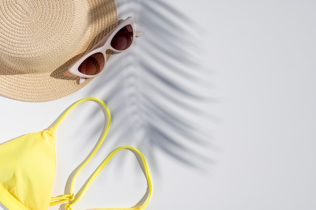 Летние каникулы минимальная плоская планировка. модные тени пальмовых листьев над соломенной шляпой, солнцезащитными очками и бикини со свободным пространством для текста. шаблон для дизайна. макет вид сверху