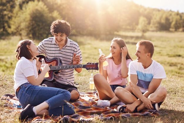Лето, отпуск, музыка и отдых концепции времени. веселые четверо друзей или одноклассников устраивают пикники на свежем воздухе, поют песни под гитару, пьют энергетические напитки, наслаждаются солнечным теплым днем, позируют на поле