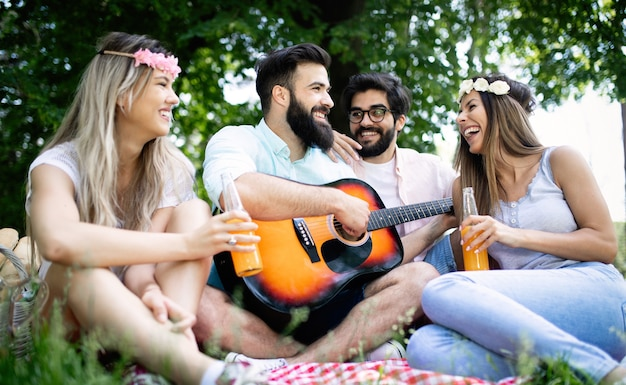 Summer, vacation, music and recreation time concept. group of friends have picnic outdoor.