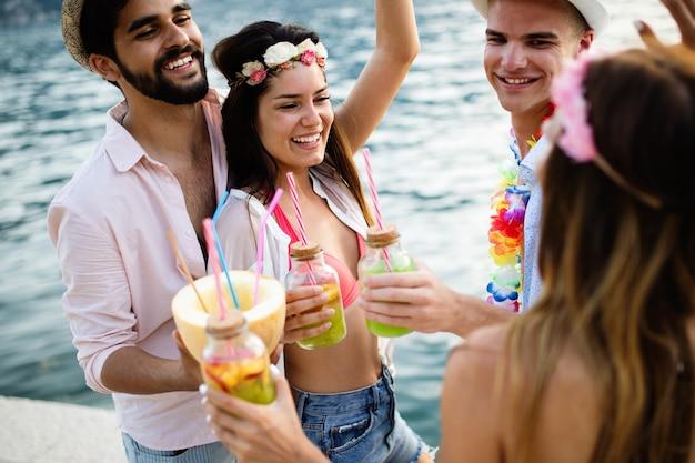 夏、休暇、パーティー、人々の概念。ビーチで楽しんでパーティーをしている友人のグループ。