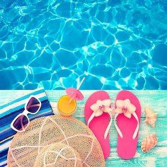 夏休み。スイミングプールのそばのピンクのサンダル。波、テクスチャ水と青い海面。デザインのためのフラットモックアップ。