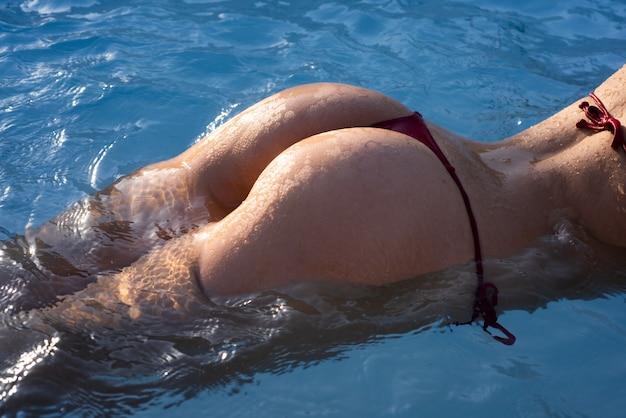 Летние каникулы сексуальная женщина, попка, ягодицы, девушка в бикини на фоне морской воды с ...