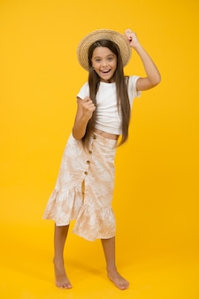 여름 방학. 여름 해변 패션. 어린 시절의 행복. 작은 소녀는 밀짚 모자를 착용합니다. 노란색 배경에 쾌활 한 아이입니다. 휴가 및 휴가 시간. 파티 재미. 평온하고 행복한 아이 맨발.