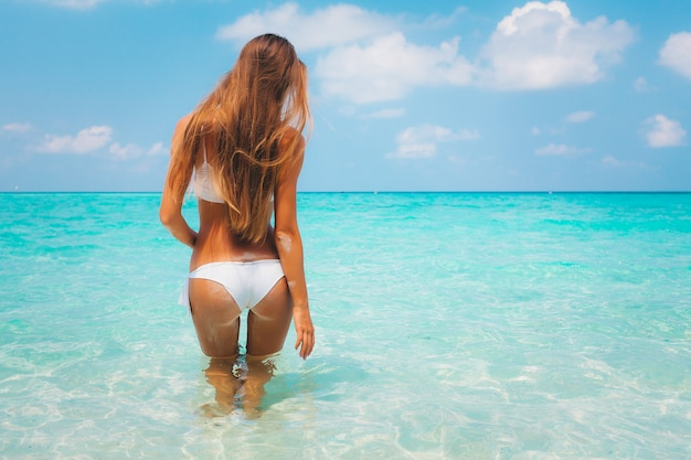 Summer vacation time - back view of sexy caucasian blonde in bikini on blue lagoon white sand beach