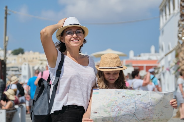 Summer vacation together, family mother and little child daughter traveling, reading map, background walking people tourists, sunny day