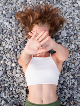 Summer vacation. top view of young smiling woman in swimsuit lying on stone beach, covering face with hands. selective focus