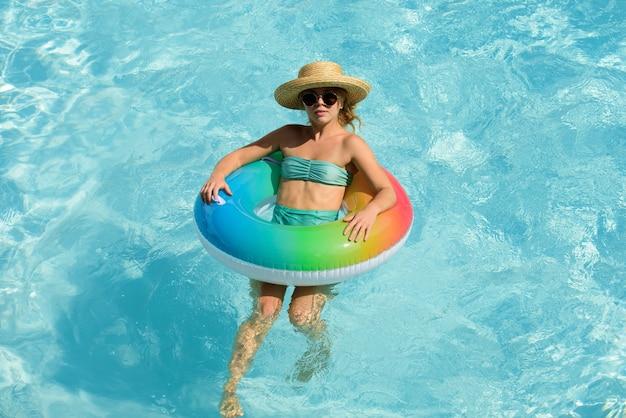 Летний отпуск. женщина в бассейне. развлекаемся в аквапарке. качающаяся девушка на надувном резиновом круге. лето.