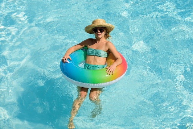 Summer vacation. woman in swimmingpool. having fun at aquapark. swiling girl on inflatable rubber circle. summertime.