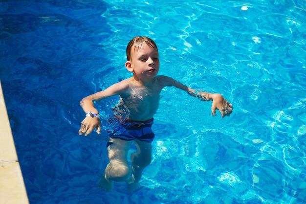 夏休みのコンセプト。プールの水で泳ぐかわいい男の子。しぶきとプールで楽しんでいる子供