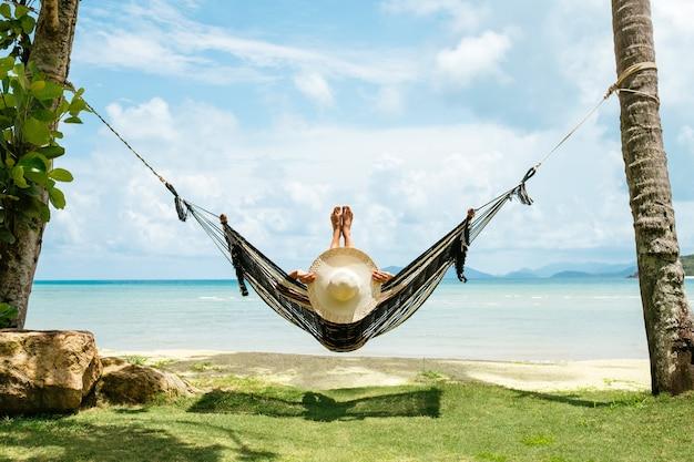 夏休みのコンセプト。熱帯のビーチのハンモックでリラックスした黒ビキニの幸せな女性