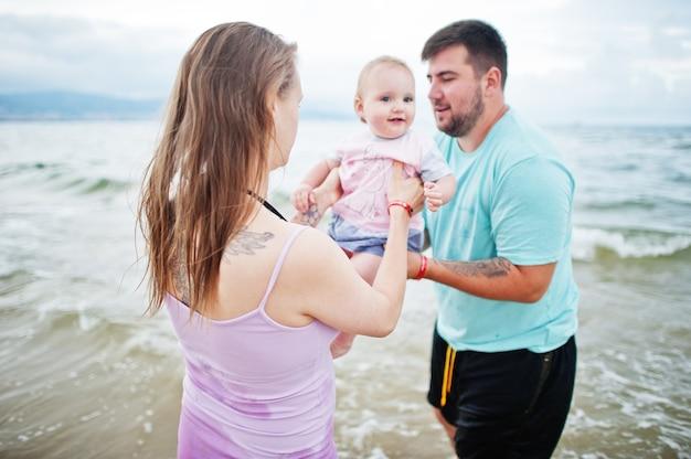 夏休み。親と子供との野外活動。幸せな家族の休日。父、妊娠中の母親、海砂浜の赤ん坊の娘。