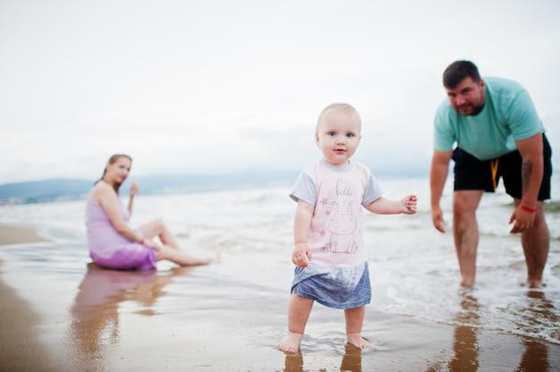 夏休み。親と子供との野外活動。幸せな家族の休日。父、妊娠中の母親、海砂浜の赤ん坊の娘。 Premium写真