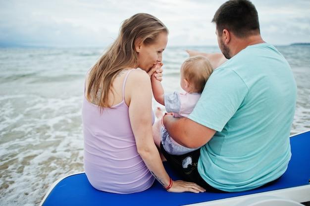 夏休み。親と子供との野外活動。幸せな家族の休日。父、妊娠中の母親、海砂浜のサンベッドに座っている赤ん坊の娘。
