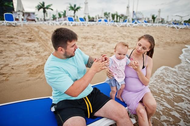 夏休み。親と子供との野外活動。幸せな家族の休日。父、妊娠中の母親、海砂浜のサンベッドに座っている赤ん坊の娘。 Premium写真