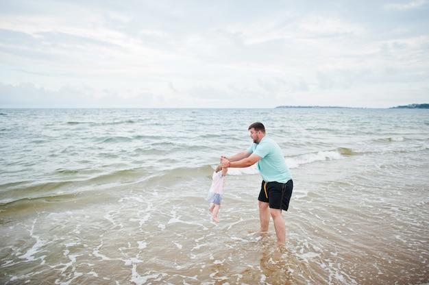 夏休み。親と子供との野外活動。幸せな家族の休日。海砂浜で赤ん坊の娘と父。